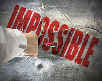 Punching, break concrete wall with word impossible on it, make i. T possible Stock Photos
