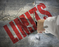 Punching, cracked concrete wall with word LIMITS on it and small. Pieces rock flying out Stock Photos
