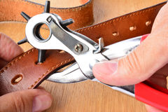 Punching holes on leather belt Stock Image