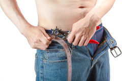 Punching a new hole in a waist belt. Weight loss achievement. Punching a new hole in a belt royalty free stock image
