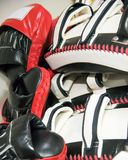 Punching Pads, Mitts, Bags and Gloves. Stack punching pads, mitts or bags lying on the blue mat after mix martial art training royalty free stock image