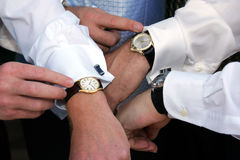 Punctual Groom. A groom and his two groomsmen synchronizing their watches before a wedding Royalty Free Stock Photo
