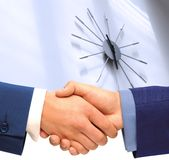Punctuality. Handshaking in front of a clock stock images
