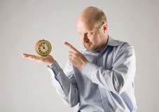 Punctuality. Man shows at clock standing on his hand, isolated on grey royalty free stock image
