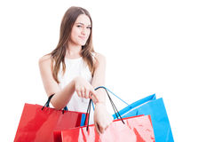 Punctuality concept with smiling beautiful shopaholic showing he. R wrist and get in time on shopping on white background with copy space stock photo