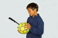 Boy With A Knife Punctured Football Ball. A very unhappy boy with a punctured football stock photo