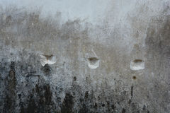 Punctured wall. An Old grungy looking wall, punctured with a chiesel in three places,aged and filled with dirt. Is a grunge textured unpainted wall stock photo