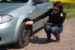 Punctured wheel. Woman and the car with punctured wheel stock photo