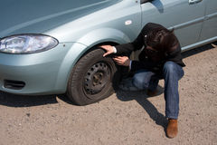 Punctured wheel. Woman and the car with punctured wheel stock images