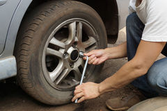 Punctured wheel. The man changes the punctured wheel of the car royalty free stock images