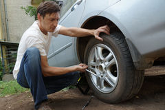 Punctured wheel. The man changes the punctured wheel of the car stock photos