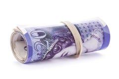 20 pund sedlar som är hoprullade och dras åt med gummibandet på Royaltyfri Fotografi