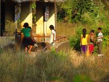 Pune, Índia - 20 de novembro de 2013: Esforço das crianças do fazendeiro ao colo fotos de stock