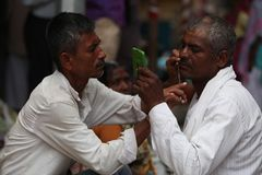 Pune, India  - July 11, 2015:A streetside barber shaves a. Pilgrim during a huge pilgrimmage in India Royalty Free Stock Photography