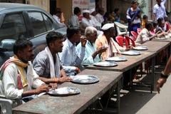 Pune, India - July 11, 2015: Indian pilgrims sitting on table on stock photography