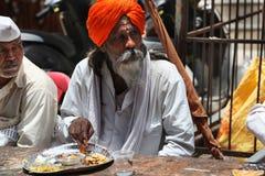 Pune, Indien - July 11, 2015: Ein hindischer Pilger, der eine Mahlzeit hat Stockbild