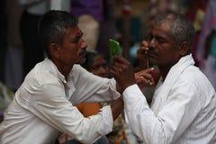 Pune, Indien - July 11, 2015: Ein streetside Friseur rasiert a lizenzfreie stockfotografie