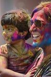 PUNE, MAHARASHTRA, ÍNDIA, o 24 de março de 2016 A mãe e a criança com pó colorido em sua cara comemoram o festival do holi em Pun Fotos de Stock