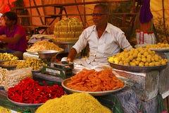 PUNE, MAHARASHTRA, Februari 2016, Verkoper verkoopt Indische snoepjes in een lokale markt stock foto's