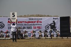 PUNE, MAHARASHTRA, INDIA, February 2018, Man shows timing board to the participants to start motorcycle race. Man showing board with timings to start dirt cross royalty free stock image