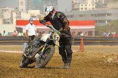 PUNE, MAHARASHTRA, la INDIA, febrero de 2018, corredor de la motocicleta coge su motocicleta caida durante la raza de la motocicl Foto de archivo