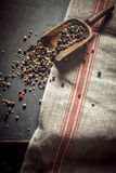 Pungent spicy dried peppercorns. In assorted black, red and white spilling out of an old wooden scoop onto a kitchen counter, overhead view with copyspace on a stock image