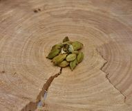 Punhado do cardamomo verde em um cruz-corte uma árvore Fotografia de Stock Royalty Free
