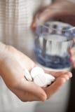 Punhado dos comprimidos e do vidro redondos brancos da água nas mãos da mulher Imagens de Stock