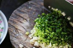 Punhado finamente - de cebolas verdes desbastadas em placa de madeira listrada Imagens de Stock Royalty Free