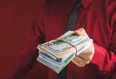 punhados do dinheiro nas mãos de um homem em um terno vermelho em um fundo vermelho fotografia de stock royalty free