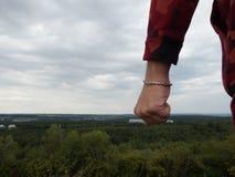 Punho apertado de um homem que está em uma montanha Fotografia de Stock