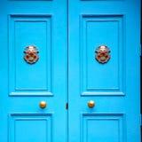 punho azul no prego de bronze oxidado da porta marrom antiga de Londres e fotografia de stock