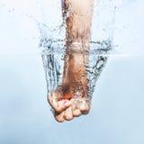 Punho da mulher através da água fotografia de stock royalty free