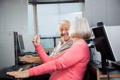 Punho de aperto da mulher ao olhar o homem na classe do computador Imagens de Stock