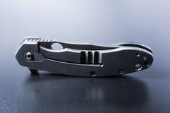 Punho de A que está a faca militar fraca na terra escura com reflexão Fotos de Stock Royalty Free