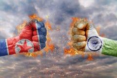 Punho dois com a bandeira da Coreia do Norte e da Índia enfrentadas em se Foto de Stock