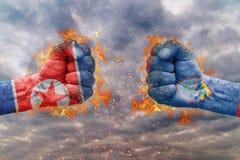 Punho dois com a bandeira da Coreia do Norte e do Guam enfrentados em se Fotos de Stock