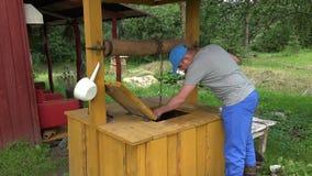 Punho masculino da polia da casa do poço da rotação do camponês a aumentar cubeta na corrente 4K filme