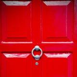 punho vermelho no prego de bronze oxidado da porta marrom antiga de Londres e no l imagem de stock