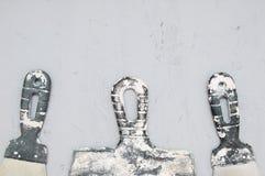 Punhos de facas de massa de vidraceiro de construção sujas em um fundo concreto fotos de stock royalty free