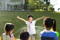 Punição do rapaz pequeno para que o pulverizador da arma de água molhe o corpo Fotografia de Stock