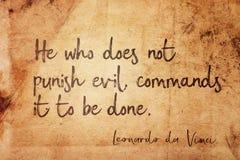 Punish evil Leonardo. He who does not punish evil, commands it to be done - ancient Italian artist Leonardo da Vinci quote printed on vintage grunge paper stock images