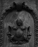 Punished character on the wood door. Shot in black and white detail of the sculpture on the facade of this historic building representing some characters / Royalty Free Stock Images