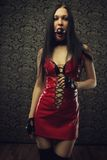 Punishment. Pretty girl in red latex dress with mouth gag stands in an empty room Royalty Free Stock Images