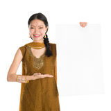 Punjabi female holding blank white paper card. Portrait of young mixed race Indian Chinese girl in traditional punjabi dress holding a blank white placard Royalty Free Stock Images