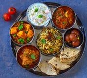 Punjabi non vegetarian thaali meals. Punjabi thali consisting of chicken pulav or pilaf, gulabjamun dessert ,roti flatbread, boondi raita ,amritsari fish curry royalty free stock images