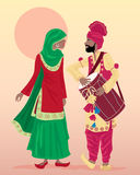 Punjabi performers. An illustration of male and female punjabi dancers dressed in traditional clothing with salwar kameez and turban playing a drum with a hot Royalty Free Stock Images