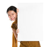 Punjabi woman holding blank white paper card. Portrait of young mixed race Indian Chinese girl in traditional punjabi dress hiding behind a blank white paper Stock Photos