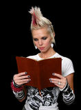 Punk With Bible. Punk Girl Reading Bible isolated over a black background stock photos