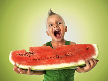 Punk boy eating a big slice of watermelon. In a green background Royalty Free Stock Photography